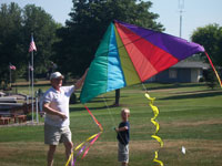 kid flying kite with grandpa
